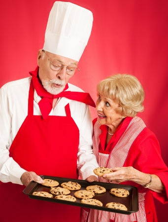 Professional baker shares a tray of fresh chocolate chip cookies with a sweet senior housewife Stock Photo - 18351351