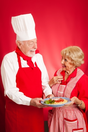 Chef teaching a sweet elderly grandma how to cook authentic Italian spaghetti marinara   Red background with copy space  photo