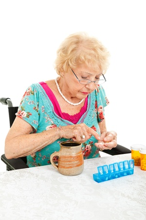 Disabled senior woman in wheelchair counting her pills into a pill container for the week   White background    photo