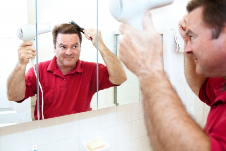 blow dryer: Man drying his hair with a hand held blow dryer in the bathroom mirror