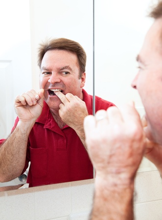 flossing: Man flossing his teeth in the bathroom mirror    Stock Photo