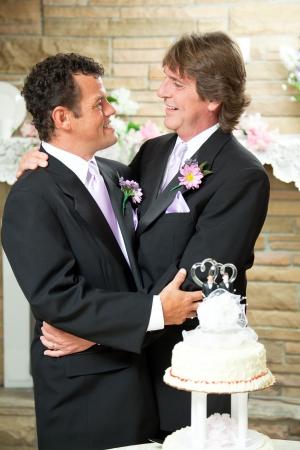 Knappe Gay paar omarmen op hun bruiloft receptie