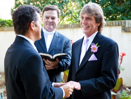Gay couple exchanging rings and vows at their wedding    photo