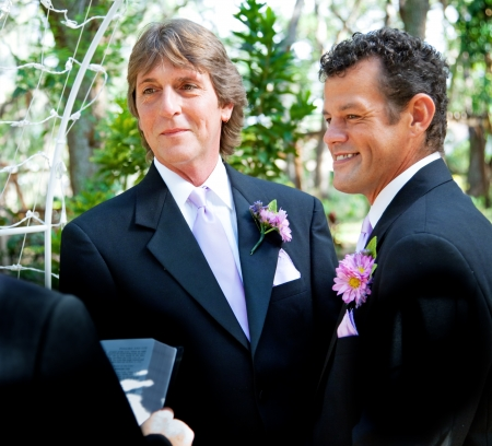 Handsome gay couple getting married in outdoor ceremony  photo