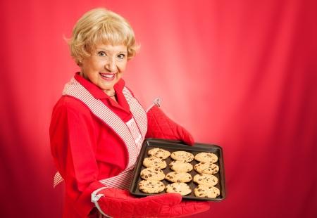 テキストのための部屋と赤い背景の上撮影の焼きたてのチョコレート チップ クッキーのパンを持って甘い愛らしい祖母 写真素材