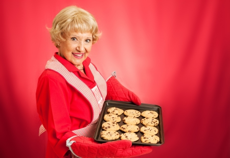 room for text: Sweet adorable grandmother holding a pan of freshly baked chocolate chip cookies    Photographed over red background with room for text
