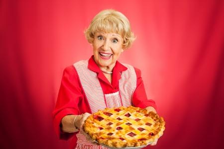 Süße retro Großmutter hält einen frisch gebackenen Gitter oben cherry pie Red Hintergrund mit viel Platz für Text