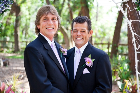 Handsome gay couple getting married under a floral archway, in outdoor ceremony    Stockfoto