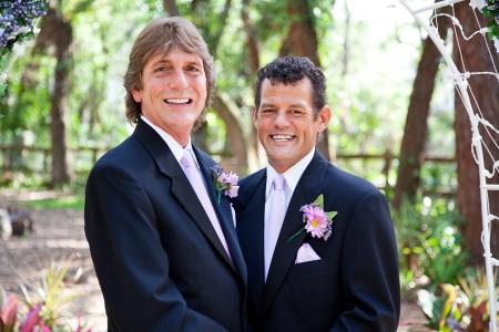 amor gay: Pareja gay guapo casarse bajo un arco de flores, en la ceremonia al aire libre