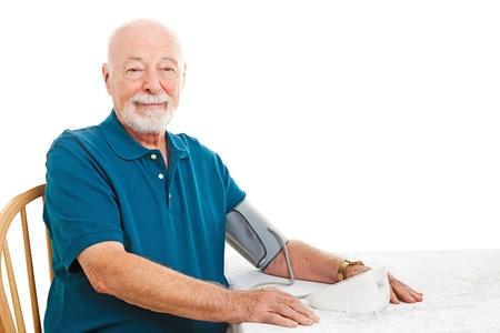 Älterer Mann, der unter seinen Blutdruck zu Hause auf dem Küchentisch Weißer Hintergrund