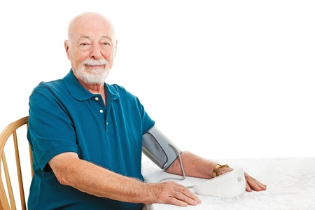 Senior man taking his blood pressure at home on the kitchen table   White background