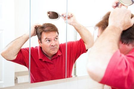 hombre calvo: Hombre de mediana edad en busca de manchas calvas en el espejo