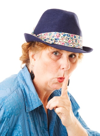 Middle-aged woman putting her finger to her lips in a hushing gesture   Isolated on white    Stock Photo