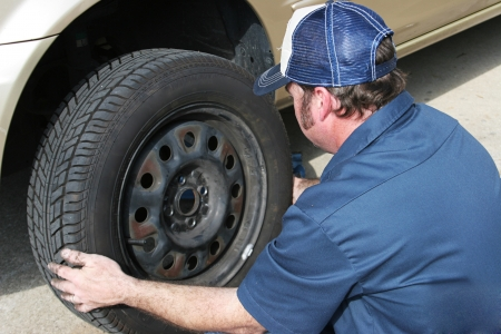 Auto mechanic removing the tire from a car.   photo