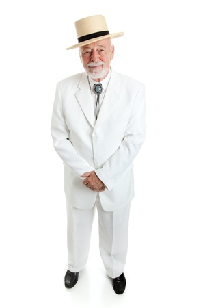 Handsome senior Southern gentleman in a white suit with a straw hat and a string tie.  Full body isolated.