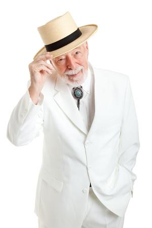 Beau gentilhomme haut du Sud dans un costume blanc et cravate ficelle, inclinant son chapeau de paille poliment. Isolé sur fond blanc.