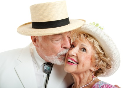 Senior couple from the American South.  He's kissing her on the cheek.  White background.