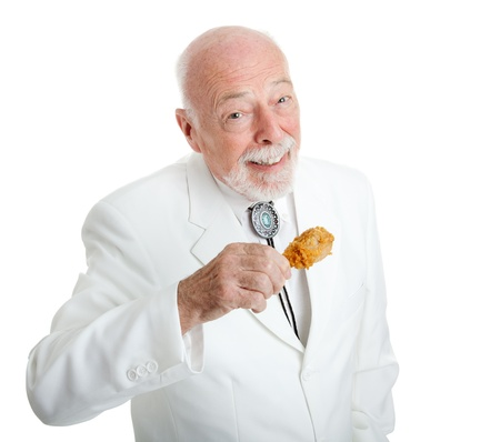 old man beard: Handsome Southern gentleman eating delicious southern fried chicken.  Isolated on white.   Stock Photo