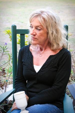 Belle femme âgée de détente dans son jardin, avec une tasse de café Elle a l'air pensif ou déprimé Banque d'images
