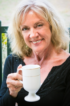 late fifties: Portrait of a beautiful woman in her late fifties, drinking a cup of coffee  Stock Photo