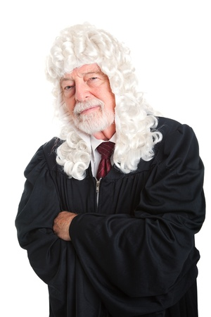 skepticism: British style judge, in a wig, with his arms crossed and a skeptical expression   Isolated    Stock Photo