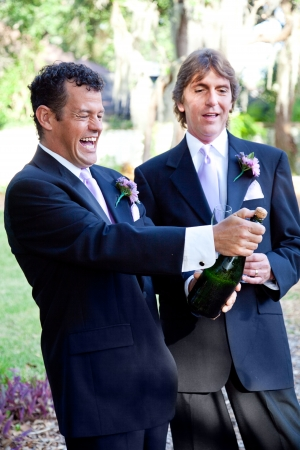 Handsome gay couple at their wedding, opening a bottle of champagne