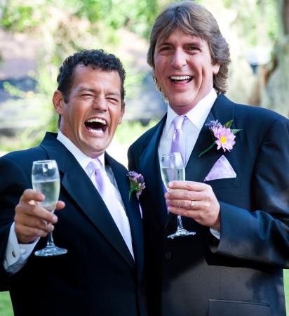 boda gay: Feliz pareja de boda gay disfrutando de champán y riendo