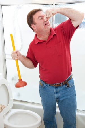 Plumber or homeowner disgusted by having to plunge toilet and holding his nose.