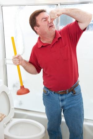 Plombier ou propriétaire dégoûté d'avoir à plonger toilette et tenant son nez.