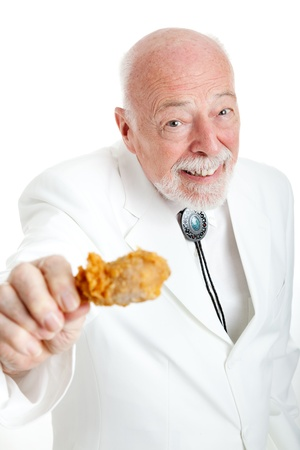 Handsome southern senior gentleman, Kentucky colonel (a generic title), eating a fried chicken leg.  White background.   photo