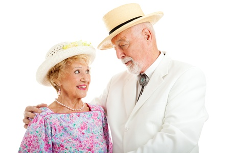 flirtatious: Handsome senior gentleman flirting with a beautiful senior lady.  Isolated on white.