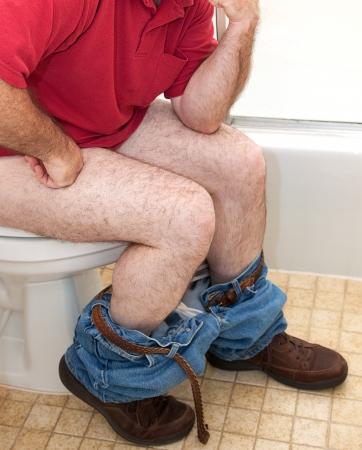 diarrea: Closupe de un hombre que piensa las cosas mientras está sentado en el inodoro.