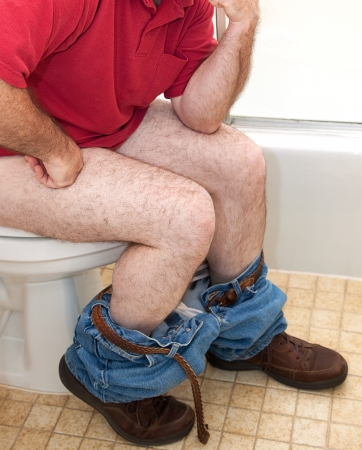 toilet: Closupe of a man thinking things over while sitting on the toilet.
