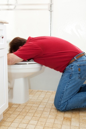 queasy: Man in the bathroom, vomiting into the toilet.