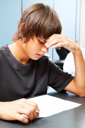 十代の少年が学校で、結果について心配している客観的なテストを取るします。 写真素材
