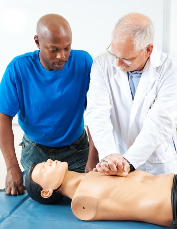 first class: Mature doctor teaching an adult student how to perform CPR, using a dummy.