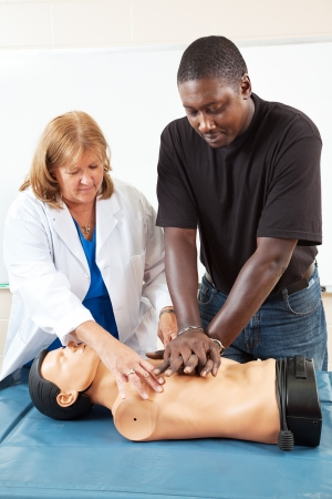 cpr: Doctor or nurse instructs an adult student in CPR life-saving techniques.