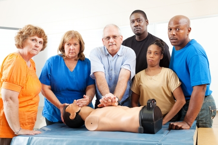 Diverse adult education class practicing CPR on a mannequin.  Serious expressions