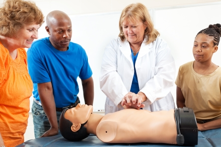 overweight students: A group of adult education students watch a doctor or nurse demonstrating CPR chest compressioon on a dummy.
