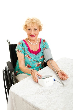 Beautiful senior woman in wheelchair taking her blood pressure with a home machine.  White background.   photo
