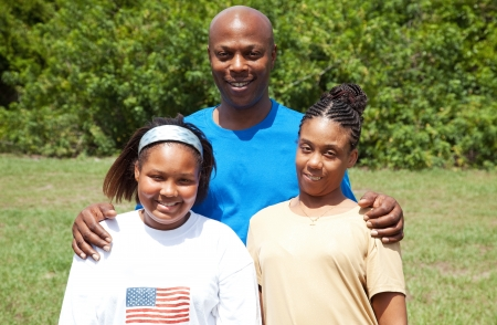 Portrait of a happy, smiling African-american family - father, mother, and daughter.  The mother has cerebral palsy.   photo