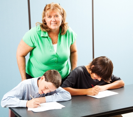 overweight students: Teacher smiling as she supervises students during academic testing.   Stock Photo