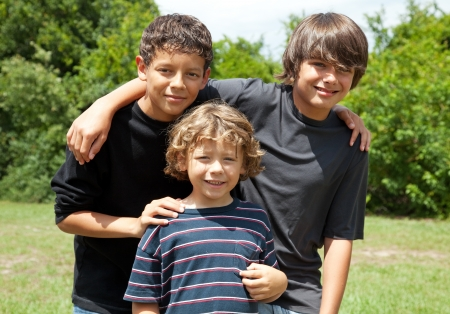 teenagers group: Three adorable boys, two adolescent friends and one little brother smiling. Diversity.   The two brothers are mixed race.