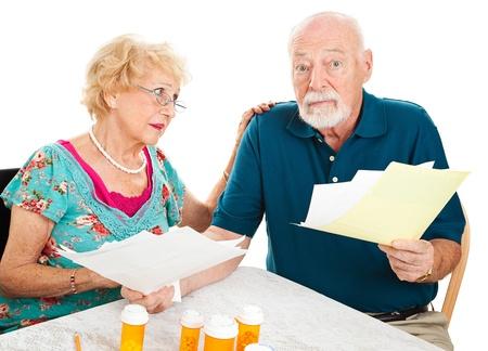 Couple de personnes âgées d'aller sur leurs factures médicales. Ils sont confus et accablé. Fond blanc.