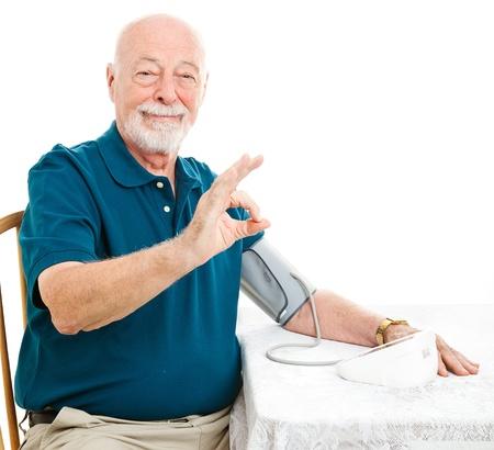 Senior homme prend sa tension artérielle à la maison et d'obtenir un bon résultat. Donner signe de la main OK. Banque d'images