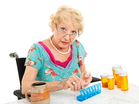 Senior woman in wheelchair sorting her weekly medications.  White background.   photo