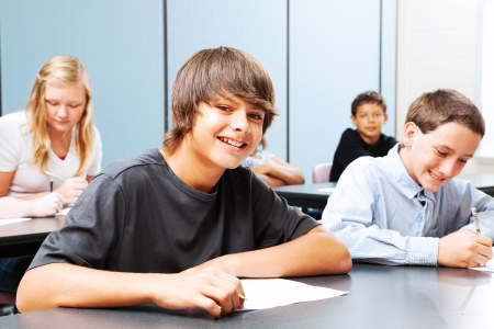 middle school: Class of teenagers in school, focus on suntanned boy in the front.   Stock Photo