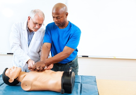 classroom training: Doctor teaching first aid CPR techniques to an adult, African-american student.  Room for text.