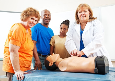 Adult students watching a nurse or doctor perform CPR on a mannequin.   Stock Photo
