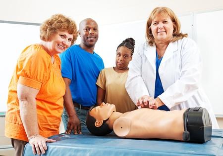 Erwachsene Schüler gerade eine Krankenschwester oder Arzt durchführen CPR auf einer Schaufensterpuppe.
